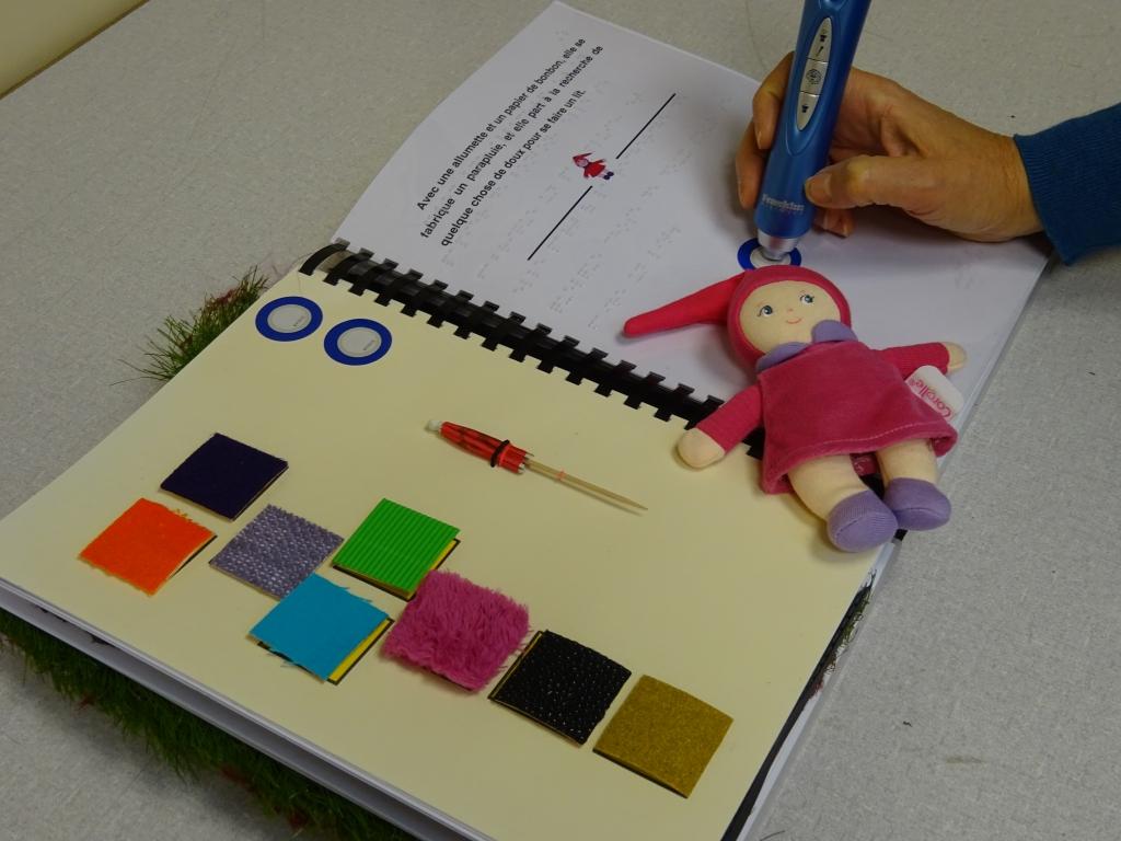 """Photo du livre tactile """"la très petite poupée"""" avec le stylo lecteur de puce RFID permettant d'avoir accès aux enregistrements sonores"""